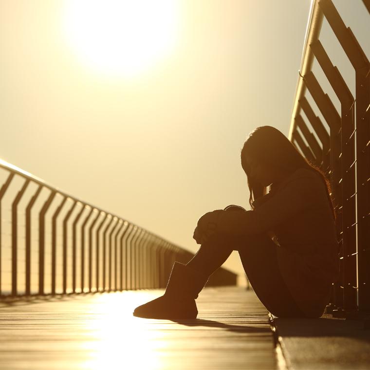 depressed teen on bridge at sunset