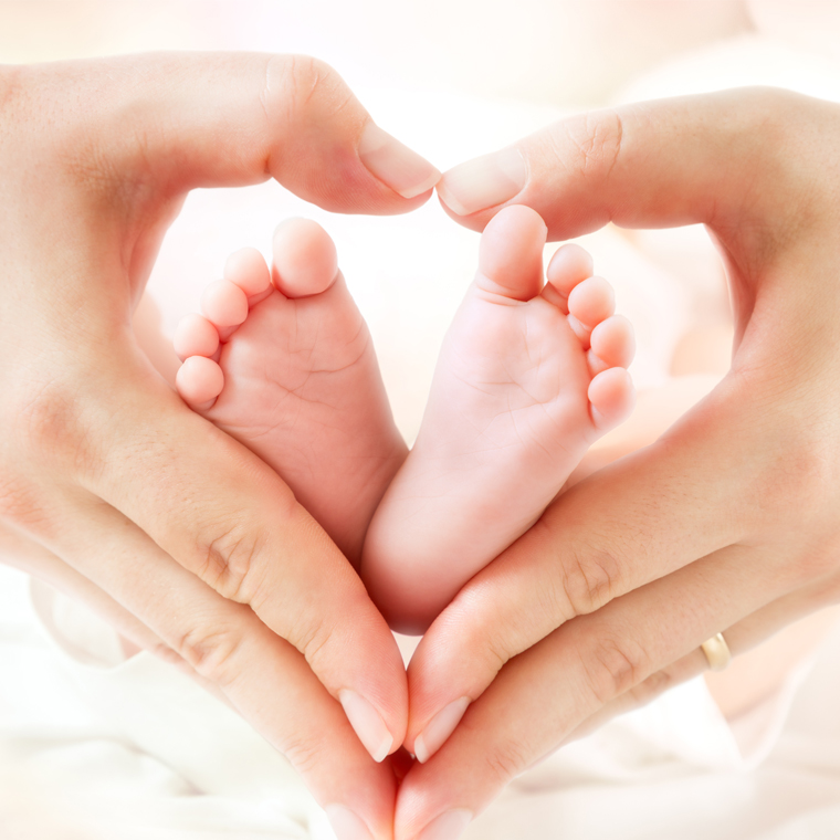 baby's feet and mom's hands in heart shape