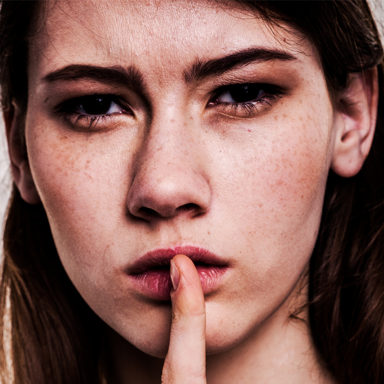 Woman placing finger against lips