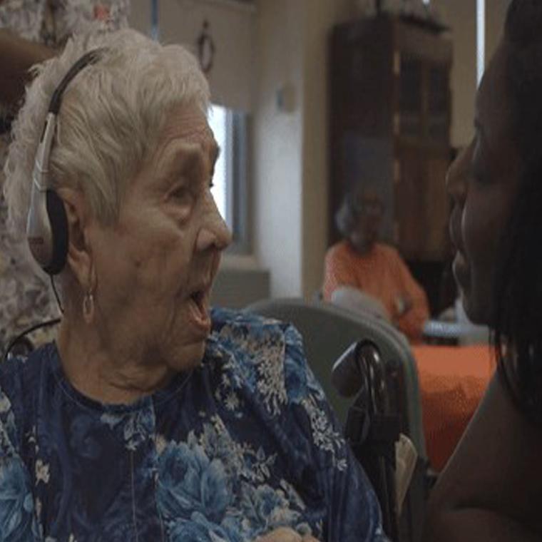 elderly woman listening to music on headphones