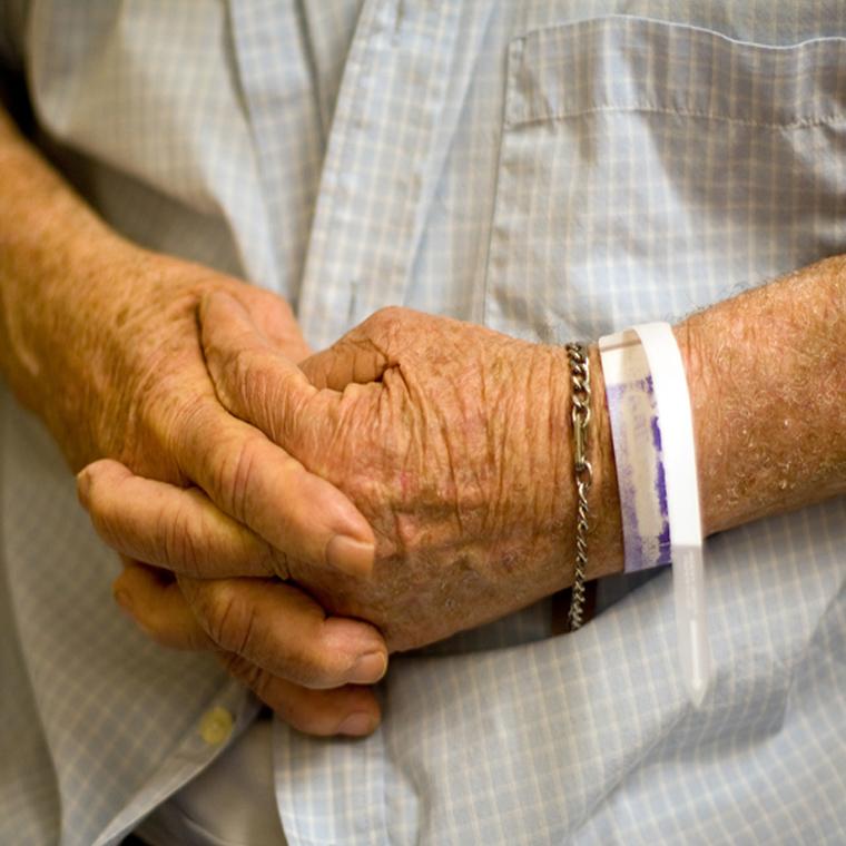 Elderly patient's hands with wristbands