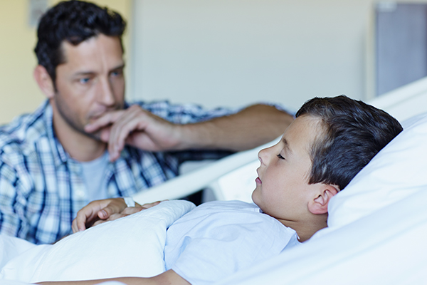 Boy in hospital bed with father nearby