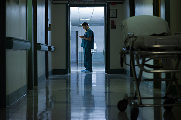 Male worker in hospital corridor looking at chart